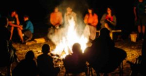 Blurred photo of people sitting around a bonfire.